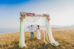 Жених и невеста у свадебной арки на фоне гор и моря
