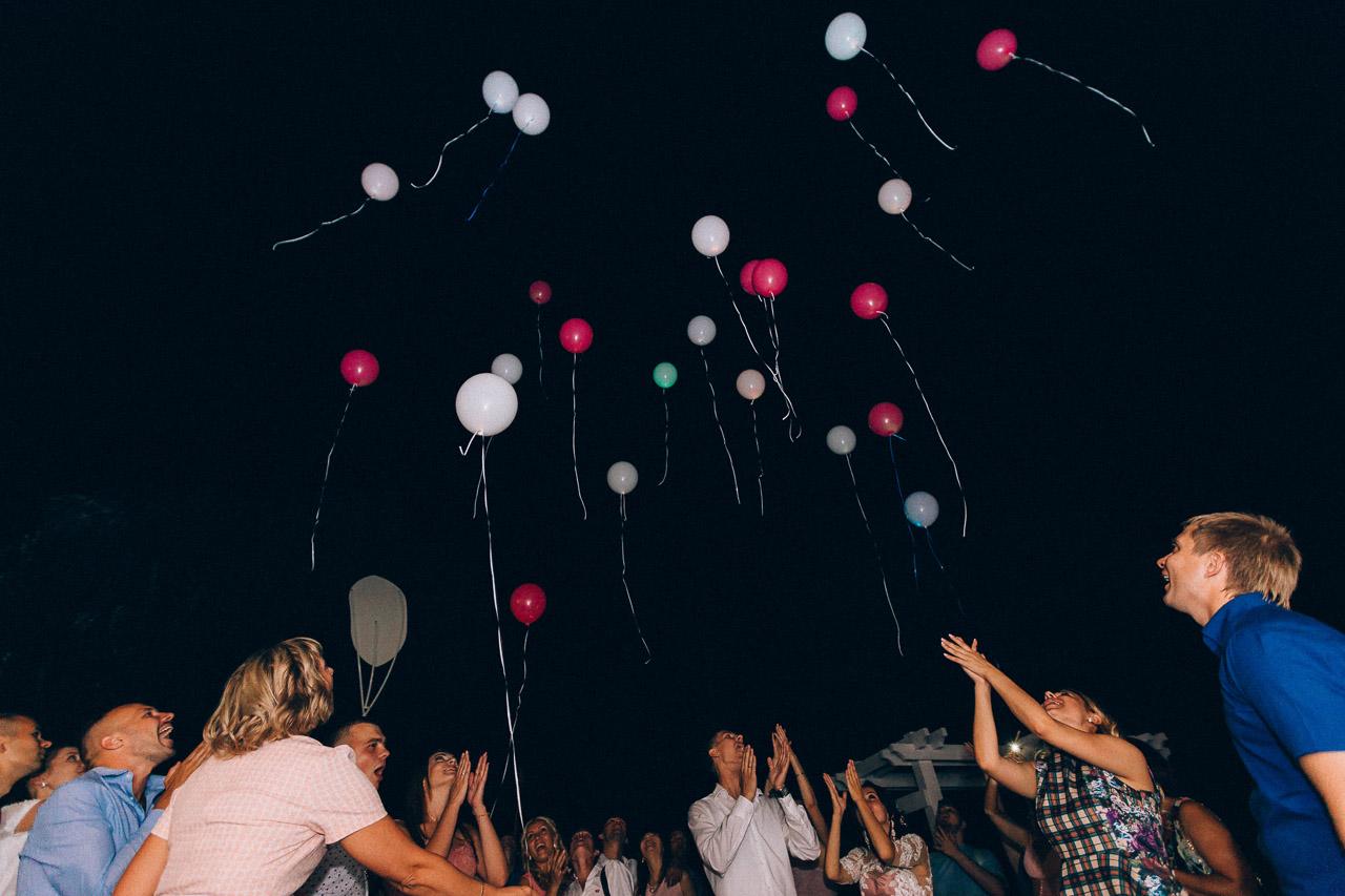 молодожены и гости запускают свадебные шары на окончании банкета